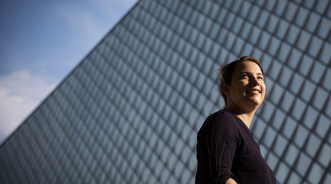 Woman stands in front of glass facade