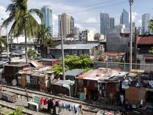 Slum in front of modern skyscrapers of the Makati financial and business district in Manila, Philippines. (Fotography: