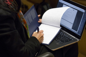 Participant with laptop and notebook at the conference (Digital) Humanities Revisited