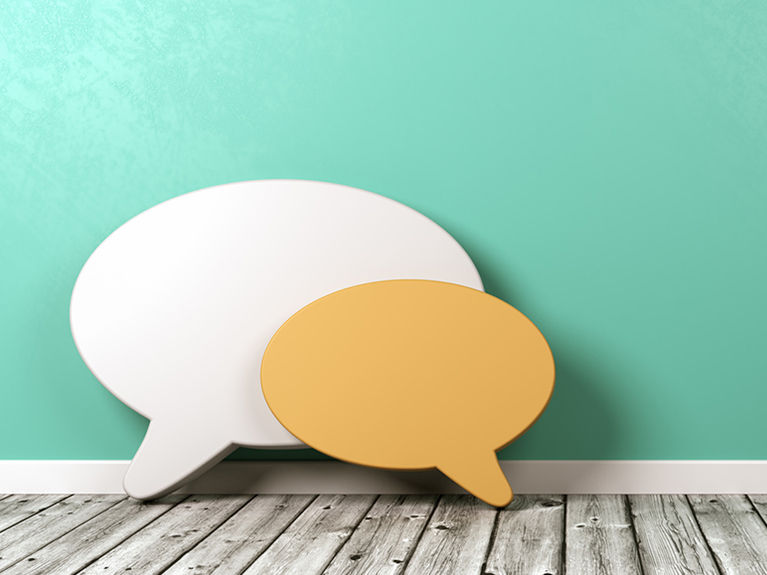 Two speech bubbles are leaning against a turquoise wall