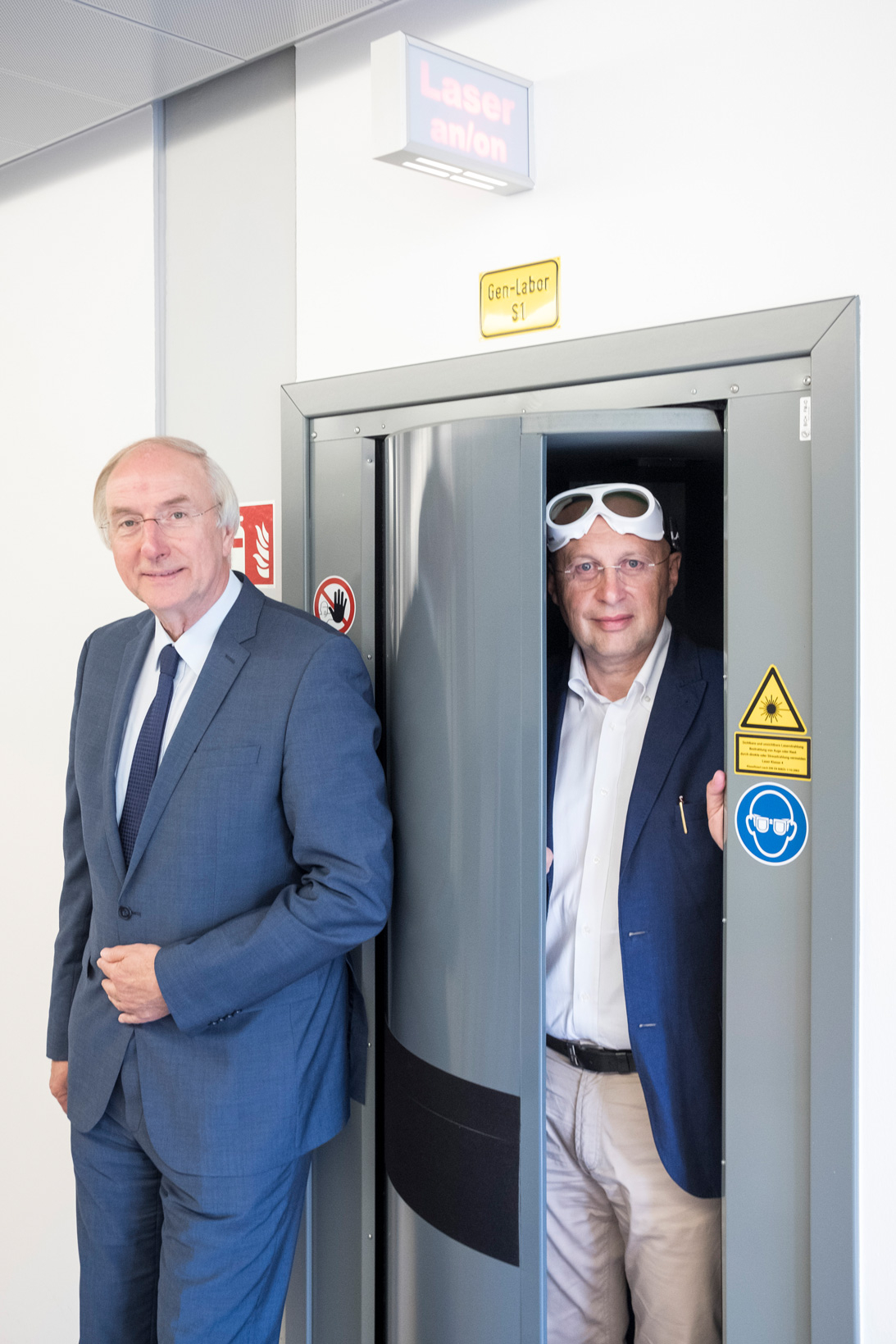 "Two men at a metal door, above the lettering ""gene laboratory"" and a sign ""Laser on"""