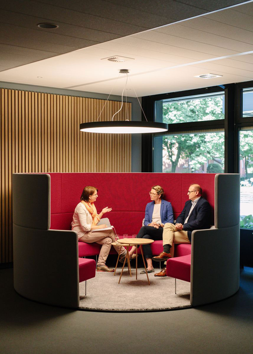 three people talking in a sitting area